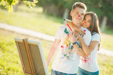 Young Beautiful Woman Embracing Her Boyfriend. Pretty Young Guys Looking At Camera And Smiling Near The Easel Outdoors, Their T-shirts Colorised By Themselves.