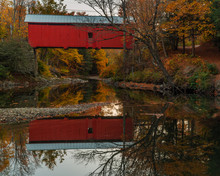 Rustic Red Covered Bridge In Autumn With Reflection