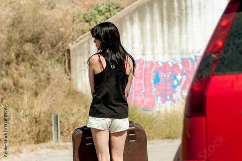 Fotografía  mujer morena con maleta y coche rojo