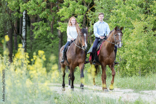 Poster Equitation Young couple enjoying horseback riding.