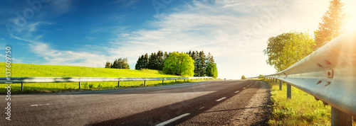 Tuinposter Lente asphalt road panorama in countryside on sunny spring evening
