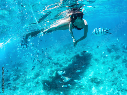 Keuken foto achterwand Duiken Beautiful woman snorkeling among fishes in blue ocean.