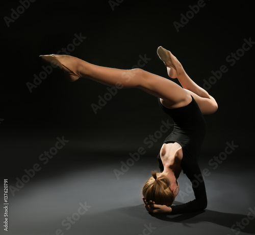 Foto op Aluminium Gymnastiek Young girl doing gymnastic exercise on dark background