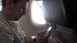 4k Interior airplane, A Caucasian passenger on a plane using his hand held electronic device phone to do some quick text messaging-Dan