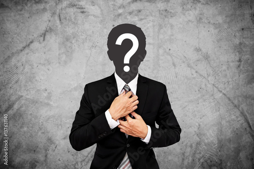 Fotografía  Businessman with question mark on head, on concrete wall background