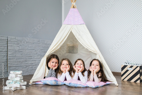 Child playing with a teepee Wallpaper Mural