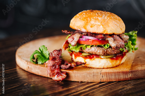 Burger with bacon, meat, tomato and lettuce   on wooden background. Close up