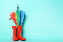 Red Rubber Boots With Umbrella On A Green Background