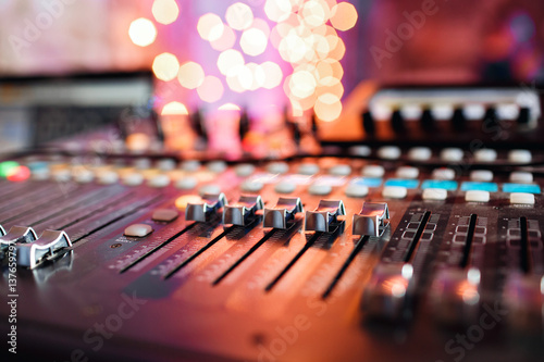 od adjusters and red buttons of a mixing console. It is used for audio signals modifications to achieve the desired output. Applied in recording studios, broadcasting, television. - 137659797