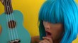 Closeup portrait of woman doing face expressions while holding ukulele and looking into the camera over yellow wall background. Creative look of woman in blue bikini and wig - slow motion video