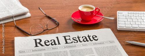 A newspaper on a wooden desk - Real Estate