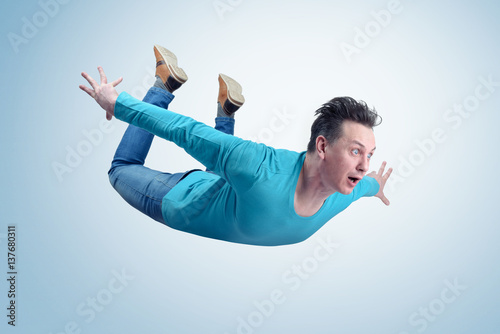 Crazy man in shirt and jeans is flying in the sky. Jumper concept