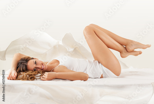 Fotografie, Obraz  Young blond hair female in underwear lying on bed and relaxing