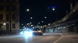 Defocused city street at night. Cars passing by