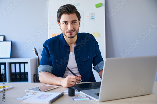 Portrait of freelance graphic designer sitting at desk with laptop and tablet