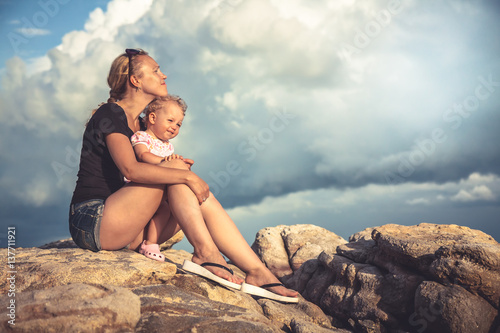 Obraz na plátně Loving young mother embrace her baby sitting on rocks with dramatic sky and clou