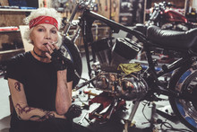 Thoughtful Old Woman Smoking Next To Bike