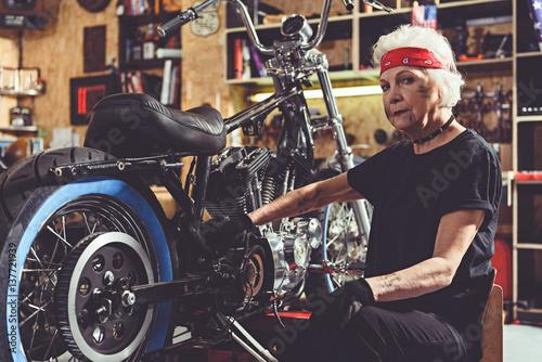 Serious retiree repairing bike in mechanic shop
