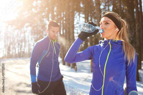 Poster Glisse hiver Girl drinks water on training in winter in forest