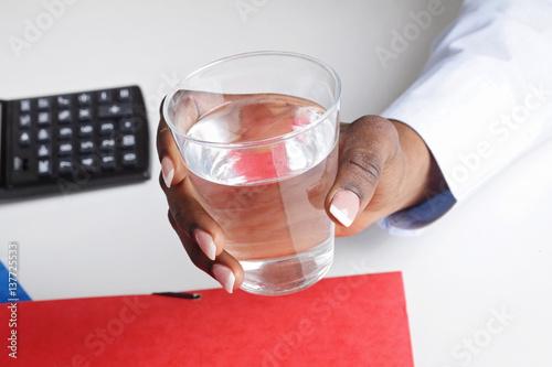 Main femme noire buvant un verre d eau au bureau buy this stock