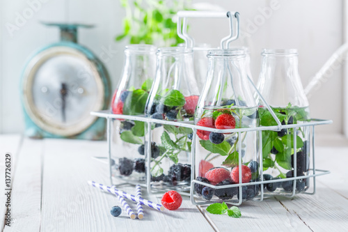 Staande foto Vlees Sparkling water in bottle with berries and mint leaves