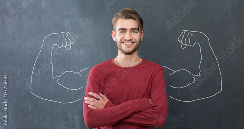 Young man against the background of depicted muscles on chalkboard Wallpaper Mural