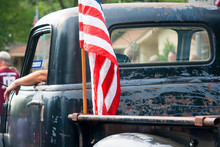 An American Flag Is Attached To The Back Of An Old, Beat Up Pickup Truck Driving In An Independence Day Parade.