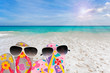 beach shoes with sunglasses on tropical sea and sky background.