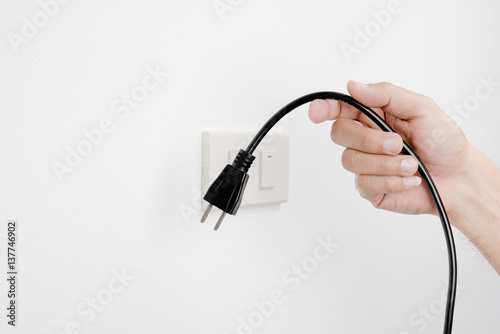 Pinturas sobre lienzo  Hand of man unplug electric outlet plug on wall white background safety concept