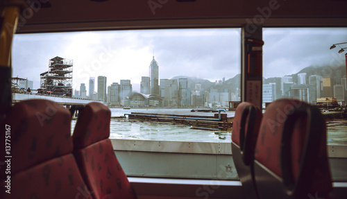 Foto op Aluminium Stad gebouw The skyscrapers of Hong Kong in background while ferry boat sail.
