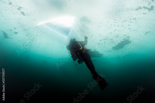 Spoed Foto op Canvas Duiken Scuba diver looking at ice hole, while ice diving