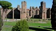 Exterior of the Baths of Caracalla seen across green lawns in Rome, Italy.