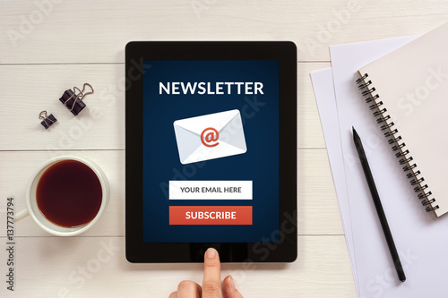 Fotografía  Subscribe newsletter concept on tablet screen with office objects on white wooden table