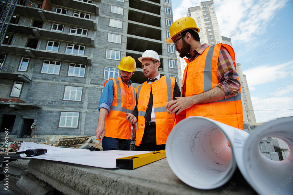 Fototapeta Low angle portrait of two workmen showing apartment building blueprints to inspector on construction site, all wearing reflective orange vests and hard hats