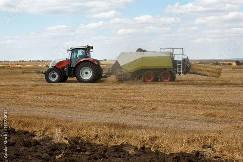 Working hay baler on a wheat field with straw dust in the air Wallpaper Mural