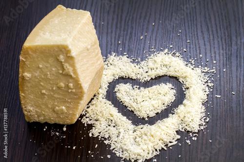 Pieces of parmigiano reggiano or parmesan cheese on black wood board