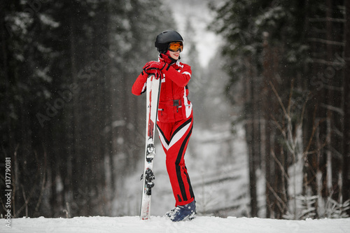 Valokuva  Girl in mask stands and holds ski during day