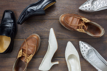 Top view  fashionable several design of men and women shoes on wooden floor with copy space.