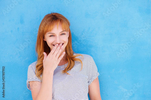 Fotografie, Obraz  happy woman laughing with hand to mouth against blue wall