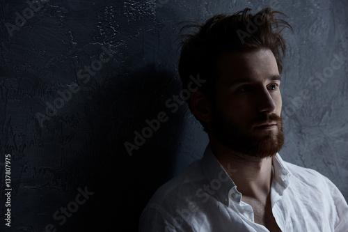 Fotografia  Sad man standing against wall