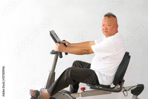 Foto op Plexiglas Fitness Senior riding spinning Exercise bike in a fitness class. Happy old man using a trainer in a gym with copy space.