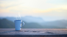 Cup With Coffee On Table Over Mountains Landscape With Sunlight. Beauty Nature Background..