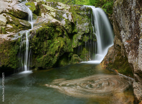 Fotobehang Watervallen Waterfall and stream in the forest mountain valley