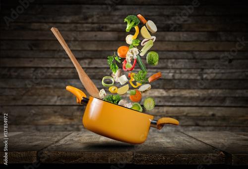 swieze-warzywa-wylatujace-z-zoltego-garnka-na-ciemnym-tle