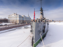 Russia, Saint-Petersburg, 10 February 2017: Aero Shootings Of A Winter Panorama Monument Of October Revolution Cruiser The Aurora At Sunset, The Nakhimov Military Naval School, Frozen River Neva