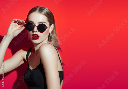 Fotomural Fashionable girl in sunglasses posing in the studio on an orange background