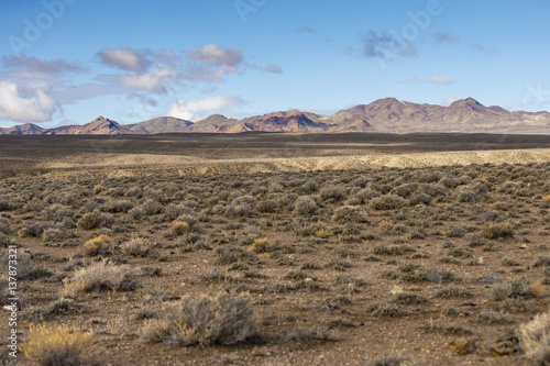 Wide open empty desert landscape in Nevada during winter with blue skies and clouds. Mountains in the distance.