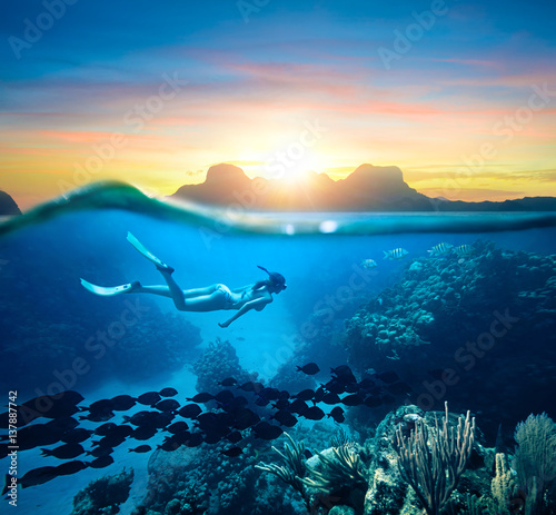 Keuken foto achterwand Duiken Woman snorkeling in clear tropical waters ocean on sunset day