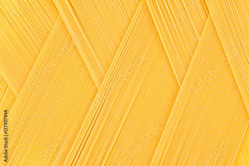 Fototapeta Italian long yellow spaghetti top view  as zigzag abstract pattern background