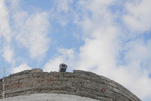 Plakat Działo na wieży (piraci, średniowieczna, przestarzała broń). Widziane z dołu. Nad czystym, błękitnym niebem.